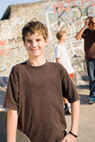 Teenager. Young teenager boy holding a skateboard with friends in the background Stock Photo