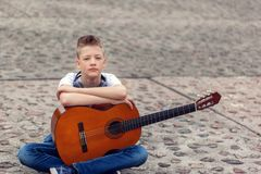 Teenager with acoustic guitar and headphones sitting in the park. Outdoors royalty free stock image