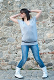 Teenager affascinante nella posa casuale contro una parete della roccia Fotografie Stock Libere da Diritti
