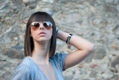 Teenager affascinante nella posa casuale contro una parete della roccia Immagine Stock Libera da Diritti
