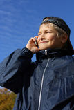 The teenager agrees on the phone. The business teenager agrees on the phone with the friends Stock Images