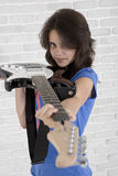 Teenager is aiming with electrical guitar like a gun Royalty Free Stock Images