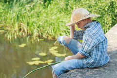 Teenager angler looking down at water from. Teenager angler is looking down at water from concrete bridge Stock Photo