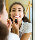 Teenager applying lipstick Royalty Free Stock Images