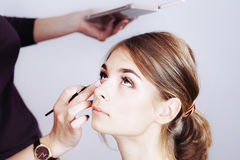 Teenager applying make-up by artist. Stock Photos