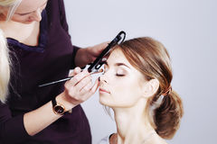 Teenager applying make-up by artist. Royalty Free Stock Photography