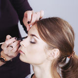 Teenager applying make-up by artist. Royalty Free Stock Images