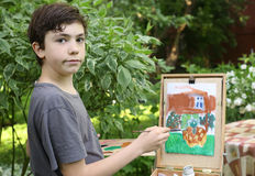 Teenager artist  boy in garden painting picture of jasmin flowers and cottage house Royalty Free Stock Image