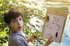 Teenager artist boy make draft sketch of pond lake in the forest Stock Image