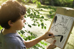 Teenager artist boy make draft sketch of pond lake in the forest Royalty Free Stock Images