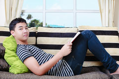 Teenager Asian Boy Laying On Sofa Royalty Free Stock Photography