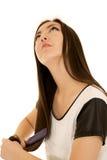 Teenager asiatico attraente spazzolando suo cercare dei capelli fotografie stock