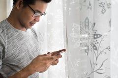Teenager asiatico facendo uso del suo smartphone nella sua stanza Immagini Stock Libere da Diritti