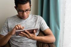 Teenager asiatico facendo uso della compressa digitale a casa Fotografie Stock