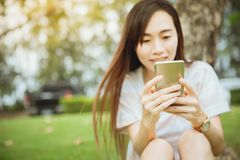 Teenager asiatico gode dello smartphone che usando il parco all'aperto si rilassa fotografia stock libera da diritti