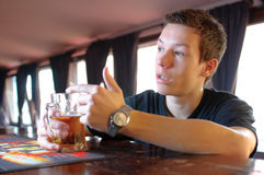 Teenager asking for another beer. Teenager sitting at a pub counter with a mug of beer in his hands and asking for another beer royalty free stock image
