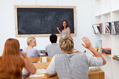Teenager asking a question in the class. Teenager asking a question to a friend in the class Royalty Free Stock Images
