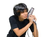 Teenager attacking w hair drier. Indian male teenager joking and smirking in attack posture with a hair drier like with a gun. Isolated over white with copy Stock Images