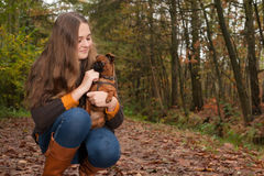Teenager in the autumn with her dog Stock Images