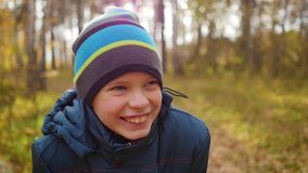 Teenager in autumn park laughs, a walk in the pine forest stock footage