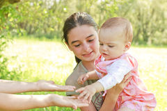 Teenager with a baby in her arms. A teenager with a baby in her arms give the child to her mother stock photography