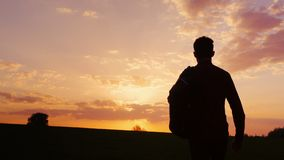 A teenager with a backpack over his shoulder goes towards the sunset in the field or in the countryside. Concept - new. A teenager with a backpack over his Stock Photography