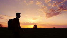 A teenager with a backpack over his shoulder goes towards the sunset in the field or in the countryside. Silhouette. Video, rear view Royalty Free Stock Photography