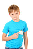 Teenager with a Badge. Sad Kid pointing on the Badge on t-shirt Isolated on the White Background Stock Photo