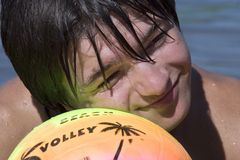 Teenager with ball on the beach. Teenager with variegated ball on the beach in summer vacation Stock Photos
