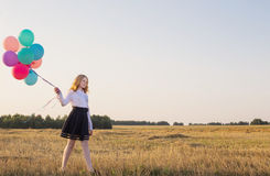 Teenager with  balloons in summer field Royalty Free Stock Photo