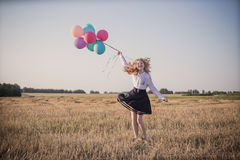 Teenager with  balloons in summer field Royalty Free Stock Images