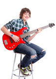 Teenager on Bass guitar sitting. Photograph showing male teenager on guitar isolated Stock Image