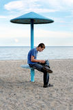 Teenager on the beach. Teenager reading letter on the empty beach Royalty Free Stock Photo