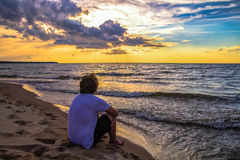 Teenager On Beach At Sunset. Male teenager on the beach during summer vacation watching the sunset over the water Stock Photo