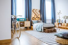 Teenager navy blue bedroom. Teenager bedroom interior with navy blue curtains, bed, bicycle, cupboard, skateboard and pillow stock photography