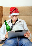 Teenager with a Beer and Tablet. Shocked Teenager in Santa Hat with Tablet Computer and Bottle of the Beer Royalty Free Stock Photo