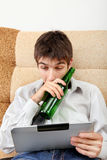 Teenager with a Beer and Tablet Royalty Free Stock Photos