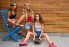 Teenager best friend girls group and skate. Teenager best friend girls group with skateboard on wood wall Stock Images