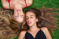 Teenager best friends girls lying down on turf. Teenager best friends girls lying down on backyard turf grass Stock Photos