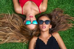 Teenager best friends girls lying down on turf. Teenager best friends girls lying down on backyard turf grass with sunglasses Stock Photography