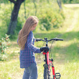 Teenager with a bicycle. Teenager girl with bicycle in countryside outdoors Royalty Free Stock Image