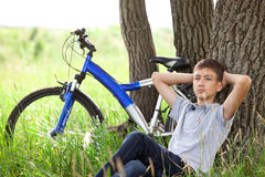 Teenager with a bicycle in the park on the grass Royalty Free Stock Photography