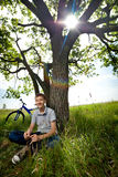Teenager with a bicycle in the park on the grass Royalty Free Stock Photos