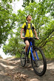 Teenager on a bicycle traveling in the forest Royalty Free Stock Photo