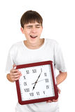 Teenager with Big Clock. Tired Teenager Yawning and holding Big Clock Isolated on the White Background Stock Photography