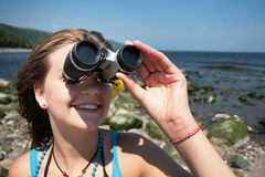 Teenager with binocular. Close up of a pretty teenager with binocular looking far away royalty free stock images