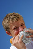 A teenager biting into a sandwich Royalty Free Stock Photos