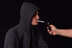 Teenager in a black hooded sweatshirt holding in his mouth a cig Royalty Free Stock Images