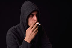 Teenager in a black hooded sweatshirt smoking a cigarette on a d Royalty Free Stock Images