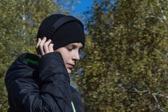 A teenager in a black jacket and hat is holding his hand on the headphones and listening to music on the background of an autumn f stock images